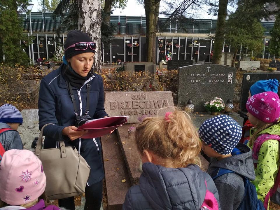 """Step in Warsaw - Stadtführerin in Warschau. Mit einer Schulgruppe auf dem Powązki-Soldatenfriedhof am Grab von Jan Brzechwa, einem der bekanntesten Autoren von Gedichten für Kinder. Wir rezitieren das Gedicht """"Am Gemüsestand"""". Warschau, Oktober 2018."""