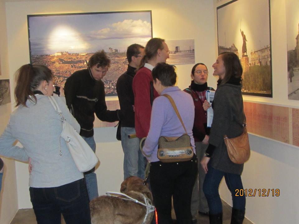 """Step in Warsaw - Stadtführerin in Warschau. Ich mache die Führung durch die Fotoausstellung von Henry N. Cobb """"1947 Die Farben der Ruinen"""" in dem Haus des Treffens mit Geschichte (Karowa Straße Nr 20). Ich weiß nicht, was so lustig war:). Warschau, Dezember 2012."""