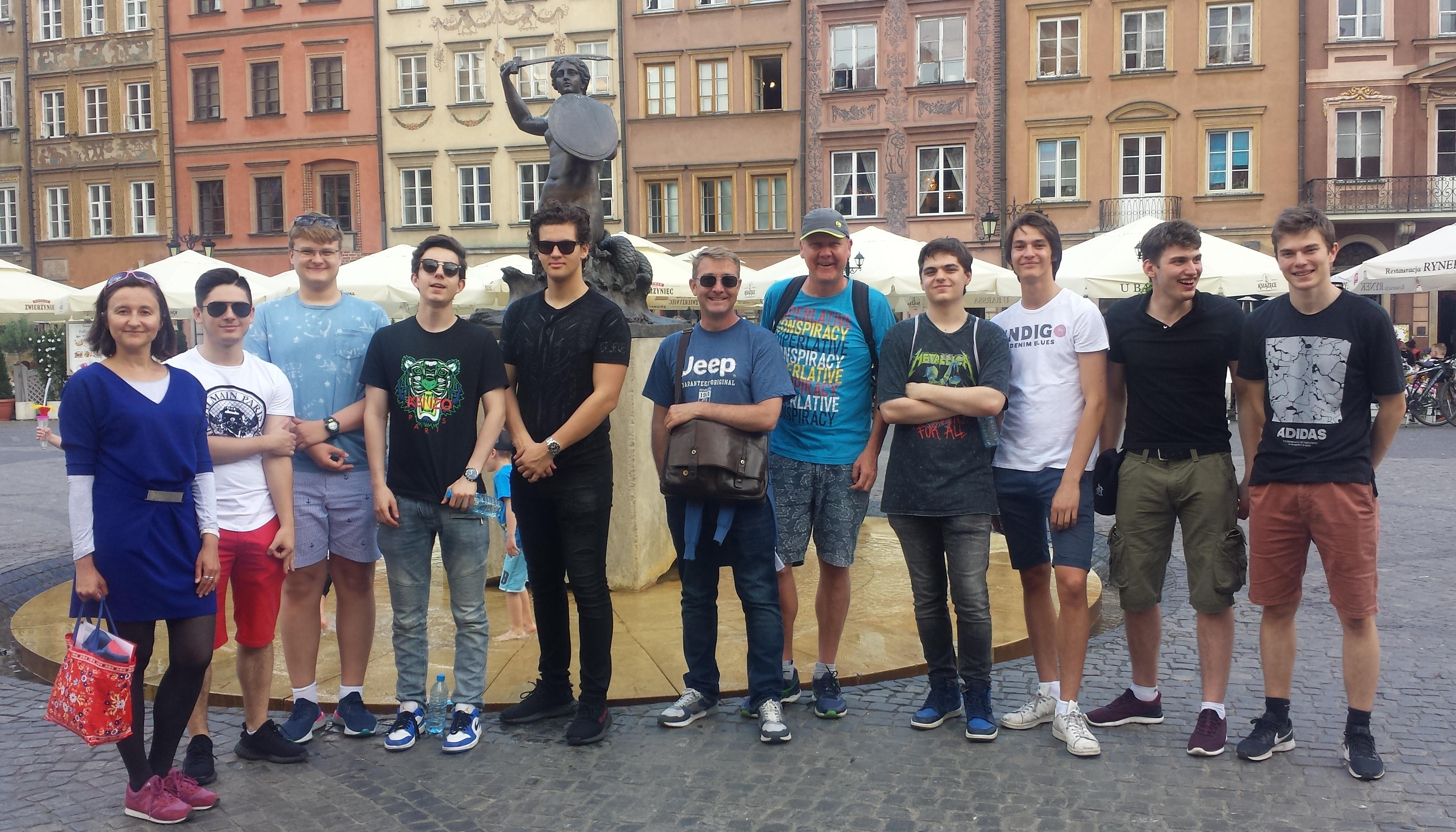 Step in Warsaw - Stadtführerin in Warschau. Die jungen internationalen Freiwilligen mit der Meerjungfrau im Hintergrund. Sie kamen nach Polen, um eine Woche im Rahmen der Organisation Habitat for Humanity zu arbeiten. Warschau-Tour vor der Reise zum Bauplatz. Warschau, 02.06.2019.