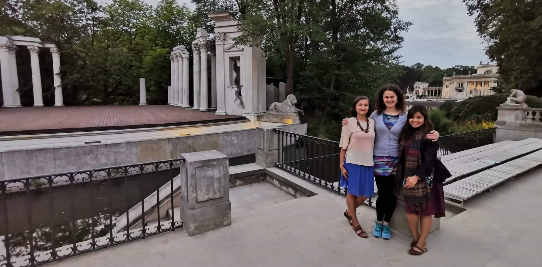 Step in Warsaw - City guide to Warsaw. A lovely tourist from Philippines is experiencing Warsaw in the company of two lovely residents of Warsaw:). Łazienki Królewskie (Royal Baths) - a summer residence of the last elective king of Poland Stanisław August Poniatowski (the 2nd half of the 18th century). The Amphitheatre in the background built as ancient ruins and modeled on the theatre of Herculaneum. The Palace on the Island in the very background. Warsaw, 23.07.2019.