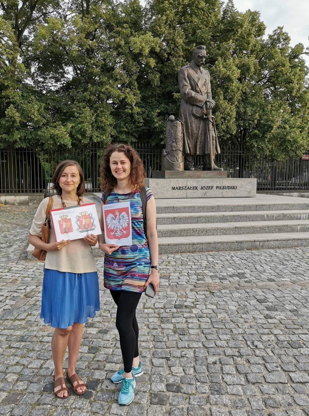 Step in Warsaw - City guide to Warsaw. A lovely tourist from Philippines is experiencing Warsaw in the company of two lovely residents of Warsaw:). Patriotic introduction: the coats of arms of Poland and Warsaw are being presented on the background of the monument of Marshal Józef Piłsudski. Warsaw, 23.07.2019.