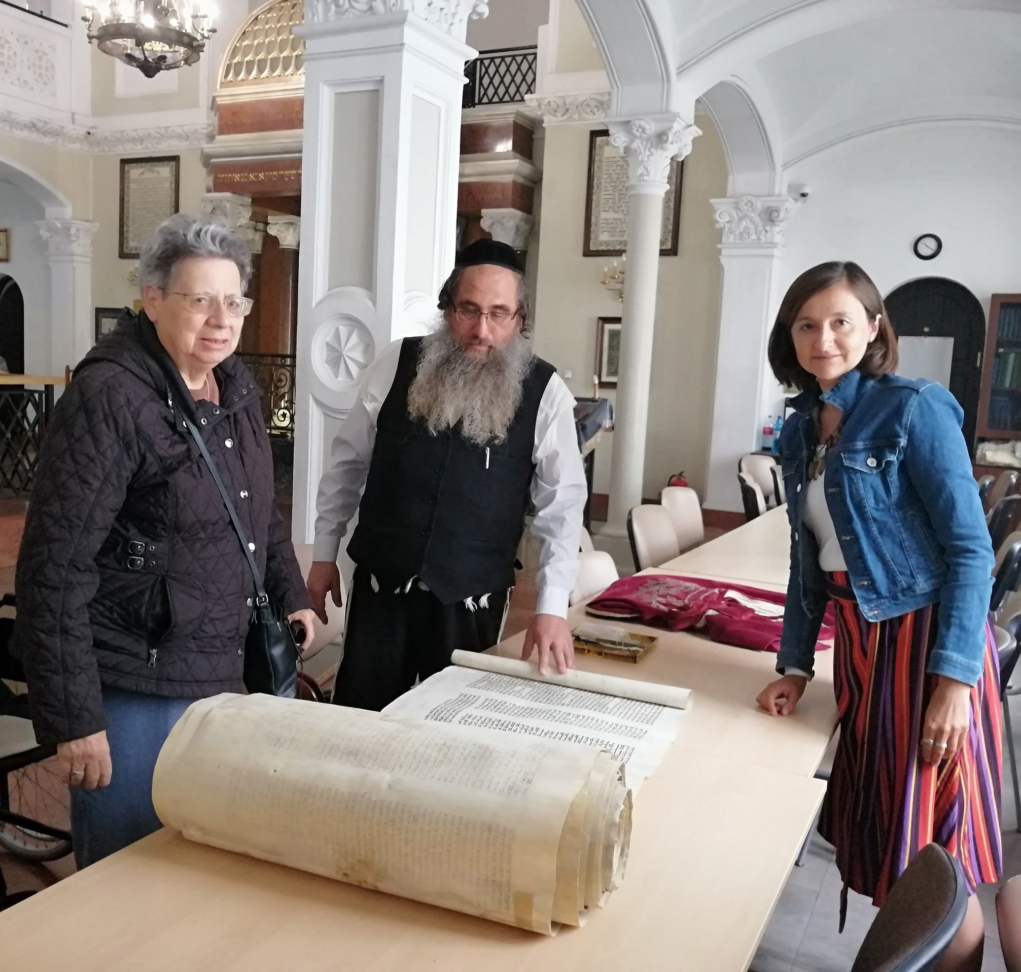 Step in Warsaw - City guide to Warsaw. An unexpected meeting with a sofer from Israel (a man who transcribes and repairs Torah) in the Nożyk Synagogue. My tourist also came from Israel. With Ruth and the sofer. Warsaw, 03.09.2019.